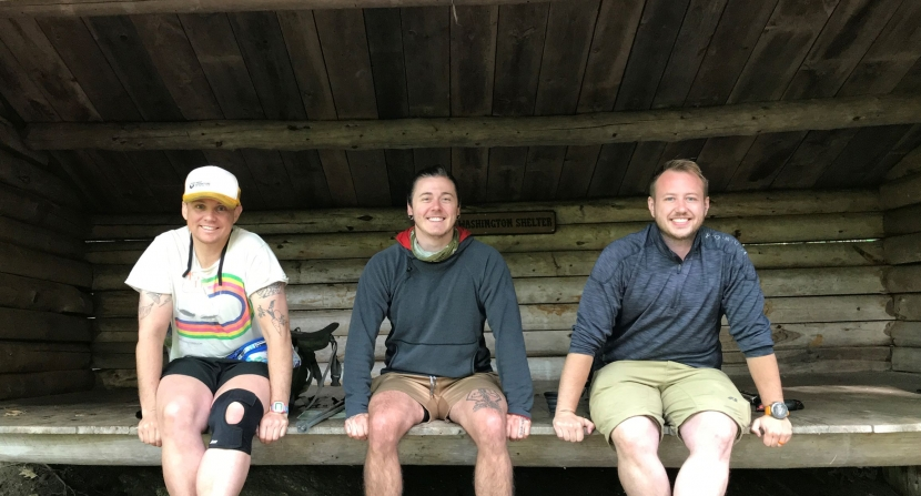 A group of three hikers sits on a bench at the General Washington Shelter on the Monadnock-Sunapee Greenway.