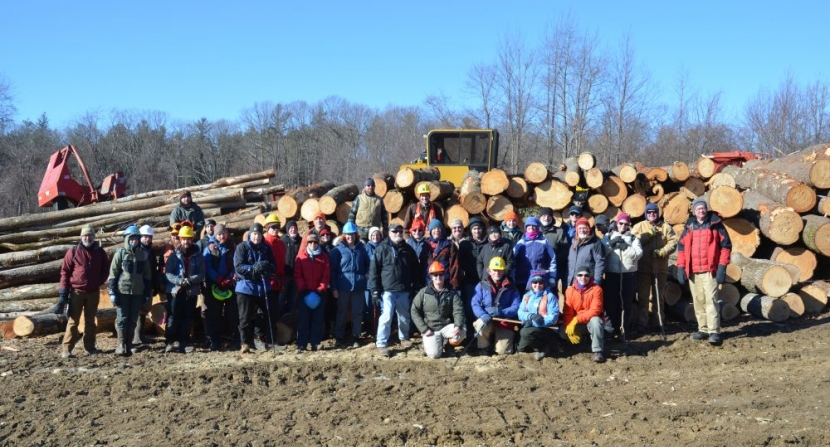 Large group in front of log pile on timber landing at Heald Tract Reservation in Wilton New Hampshire