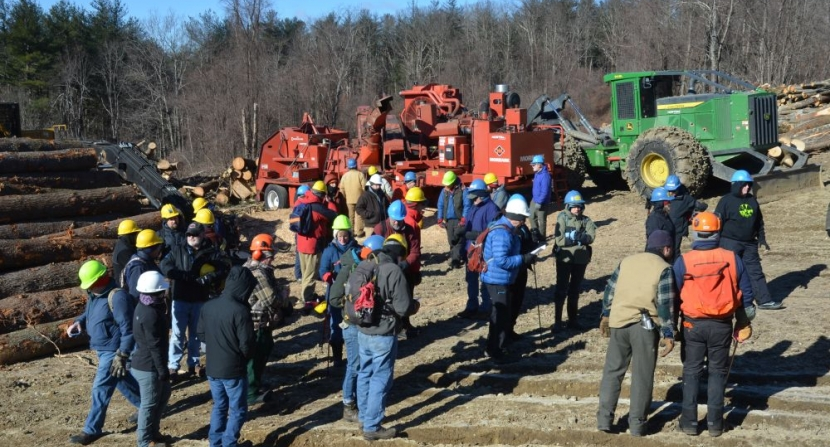 A large group gathered a timber harvest landing with a chipper and John Deere.