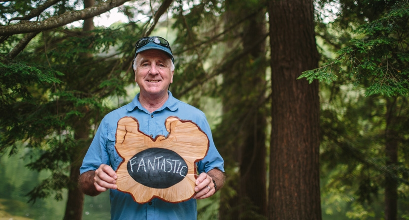 "Land Steward Ben Haubrich holding rustic tree cookie chaulkboard sign with word ""fantastic"" to summarize his volunteer experience"