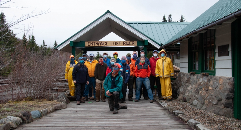 A group of volunteers in rain gear poses by the entrance to Lost River Gorge.
