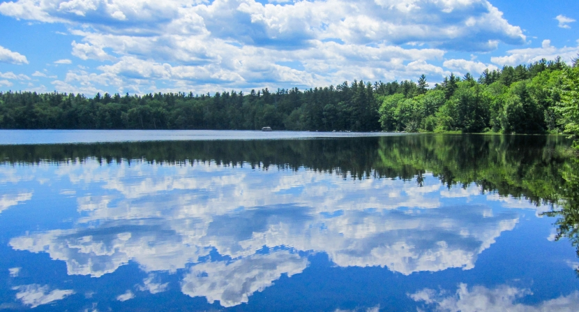 A view of Lake Massabesic in summertime with clouds reflected against the water.