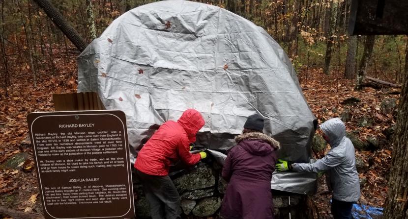 A gray tarp covers a rock foundation at Monson Village.