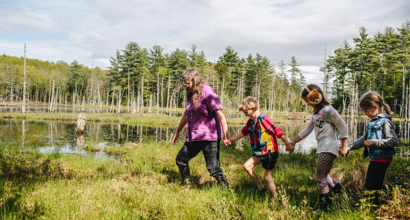 A family outing group explores sphagnum moss at a ponding event in New Durham NH