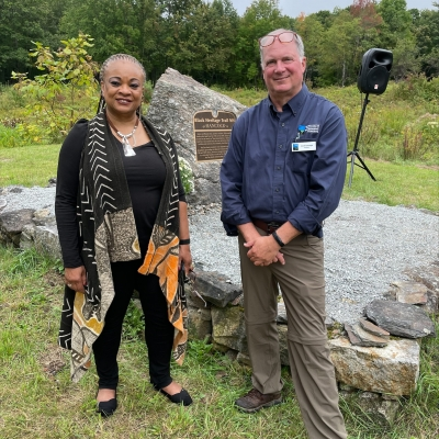 JerriAnne Boggis, Executive Director of the Black Heritage Trail of NH, and Jack Savage, President of the Forest Society, stand in front of the newly unveiled marker in Hancock under a blue sky.