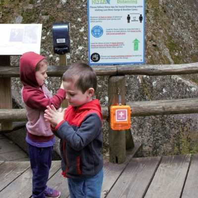 Two preschoolers wipe hands on a boardwalk near a hand sanitizing station.