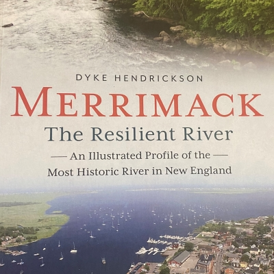 """The cover of the book """"Merrimack: The Resilient River,"""" has a photo of the river traveling by a city and flowing near a forest."""