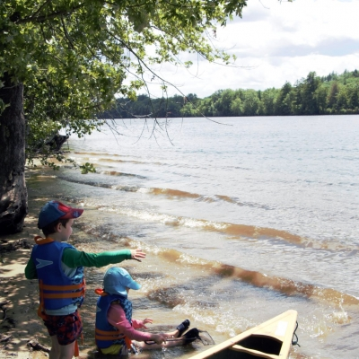 Two boys sit with their feet in the water of the Merrimack River near a forested shore.