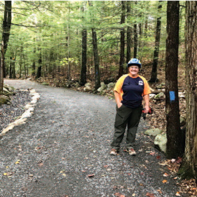 Erin Amadon, of Town 4 Trail Services LLC, poses next to the upgraded trail.