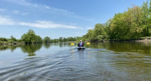 A kayaker paddles on the Merrimack River.