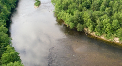 A view from above of a bend in the Merrimack River, lined with green forests.