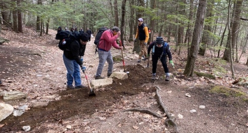Volunteers dig on the Main Trail at Mount Major as Andy Crowley supervises.