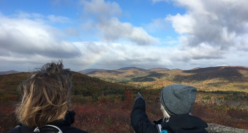 Hikers pointing to peaks of the eastern Belknap Range in Alton NH from the Forest Society Morse Preserve at the summit of Pine Mountain