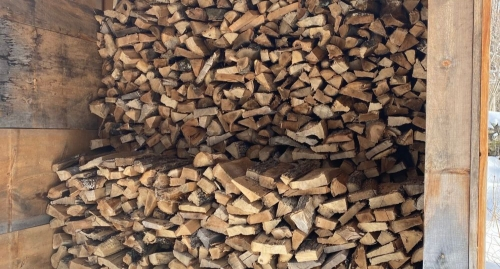 Cordwood piled neatly inside dry woodshed snow on roof