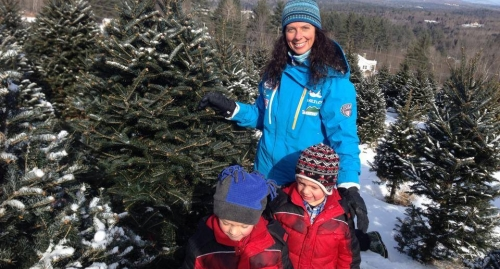 A woman and two children pose with a Christmas tree amid rows of snow-covered Christmas trees.