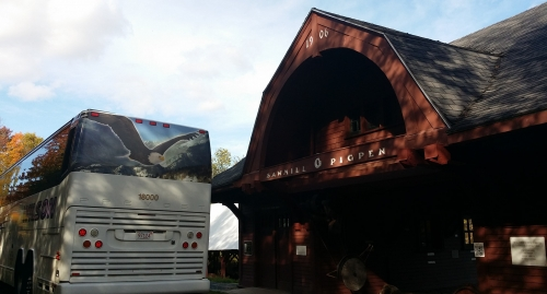 A motorcoach is parked next to the sawmill at The Rocks.