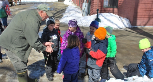 Young children gather around a guide during a maple tour.