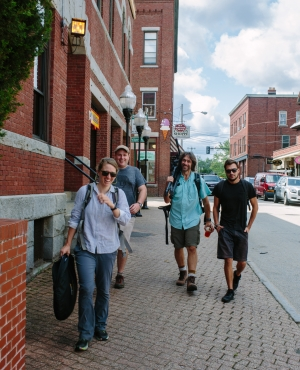 Four members of the crew of the film walk down a street in Portsmouth with their equipment.