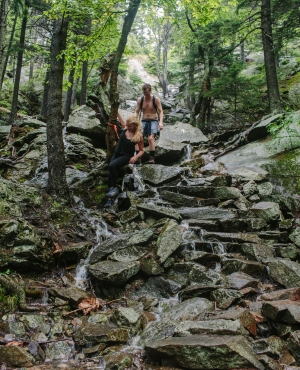 Hikers descend a dangerously slippery White Arrow trail at Monadnock State Park after heavy rain converted the path into a waterfall in July 2018.