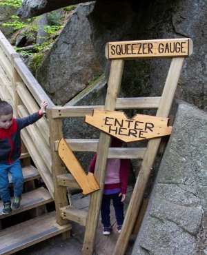 A wood sign marks the narrow passage visitors must fit through for the Lemon Squeezer cave.