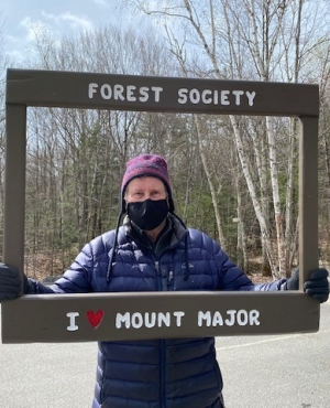 "A volunteer holds a frame up that says ""I love Mount Major"" on Earth Day."