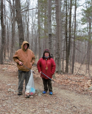 Parents hold a trash bag along the trail at Mount Major.