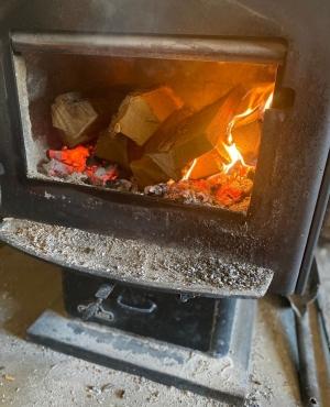 Woodstove open door reveals coals under dry logs