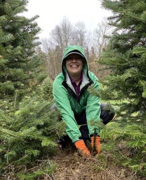 A volunteer stops to smile while planting seedlings.