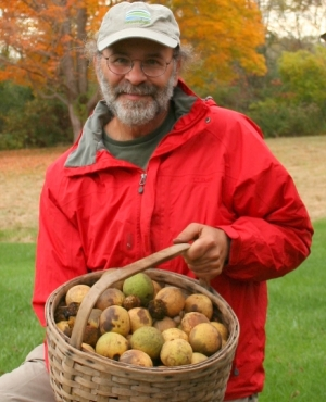 Russ Cohen holds a wicker basket heaping with black walnuts, in front of fall colors.
