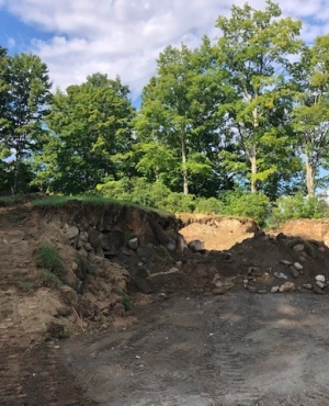 A dirt berm covered in grass and filled with soil and an old stone foundation is under construction.