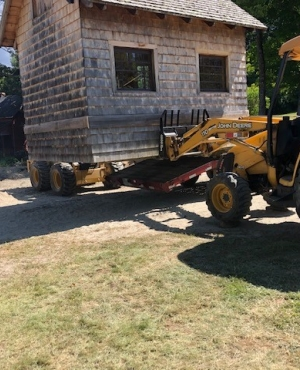A small wood shed is lifted by a front-end loader.