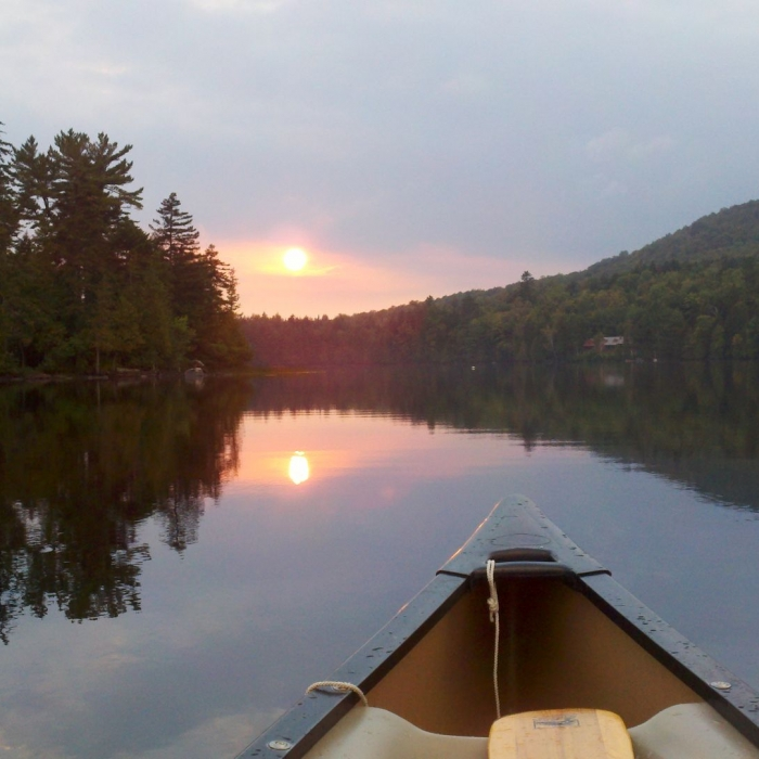Sunset view of a lake from a kayak.
