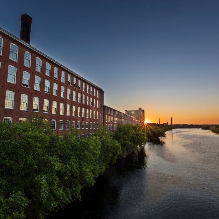 A river at sunset winds past a former mill building in Lowell.