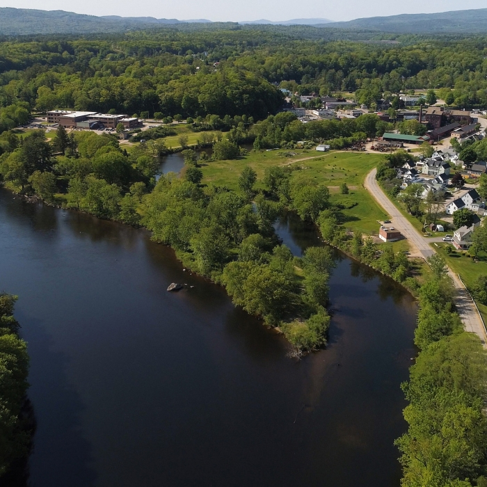A winding blue river passes the small houses and red barns that make up Franklin, New Hampshire.