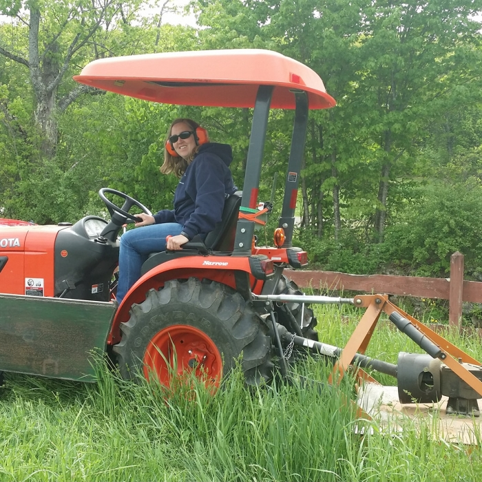 A woman on a tractor mows a field.