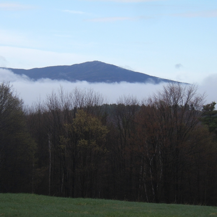 The mountain from a distance covered partially by fog.