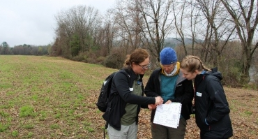 staff and volunteers look at survey in the field