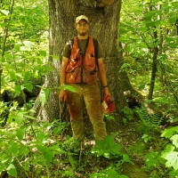 Ian Aldrich poses in front of a tree.