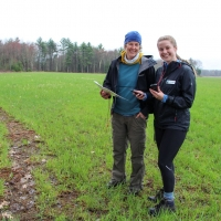 volunteers using compass and map in field smiling