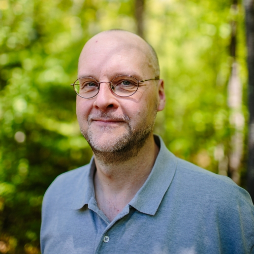 Allan Krygeris poses in the forest outside of the Conservation Center.