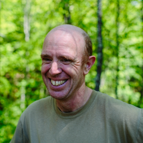 Frank Allen poses in the forest outside of the Conservation Center.