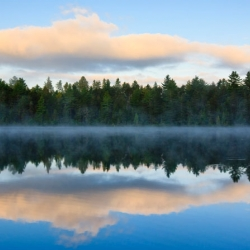 A forest and clouds are reflected in misty water below at Umbagog National Wildlife Refuge.