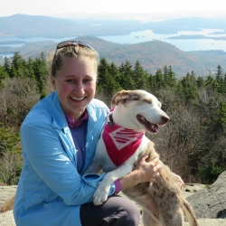 Wendy poses with her dog, Bella, with mountains in the background.